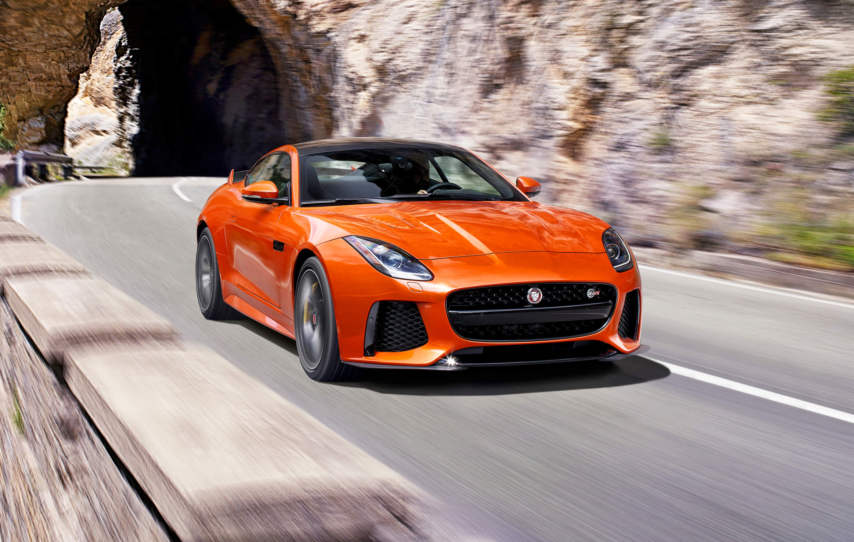 Full screen image of an orange Jaguar F-Type SVR on open roads