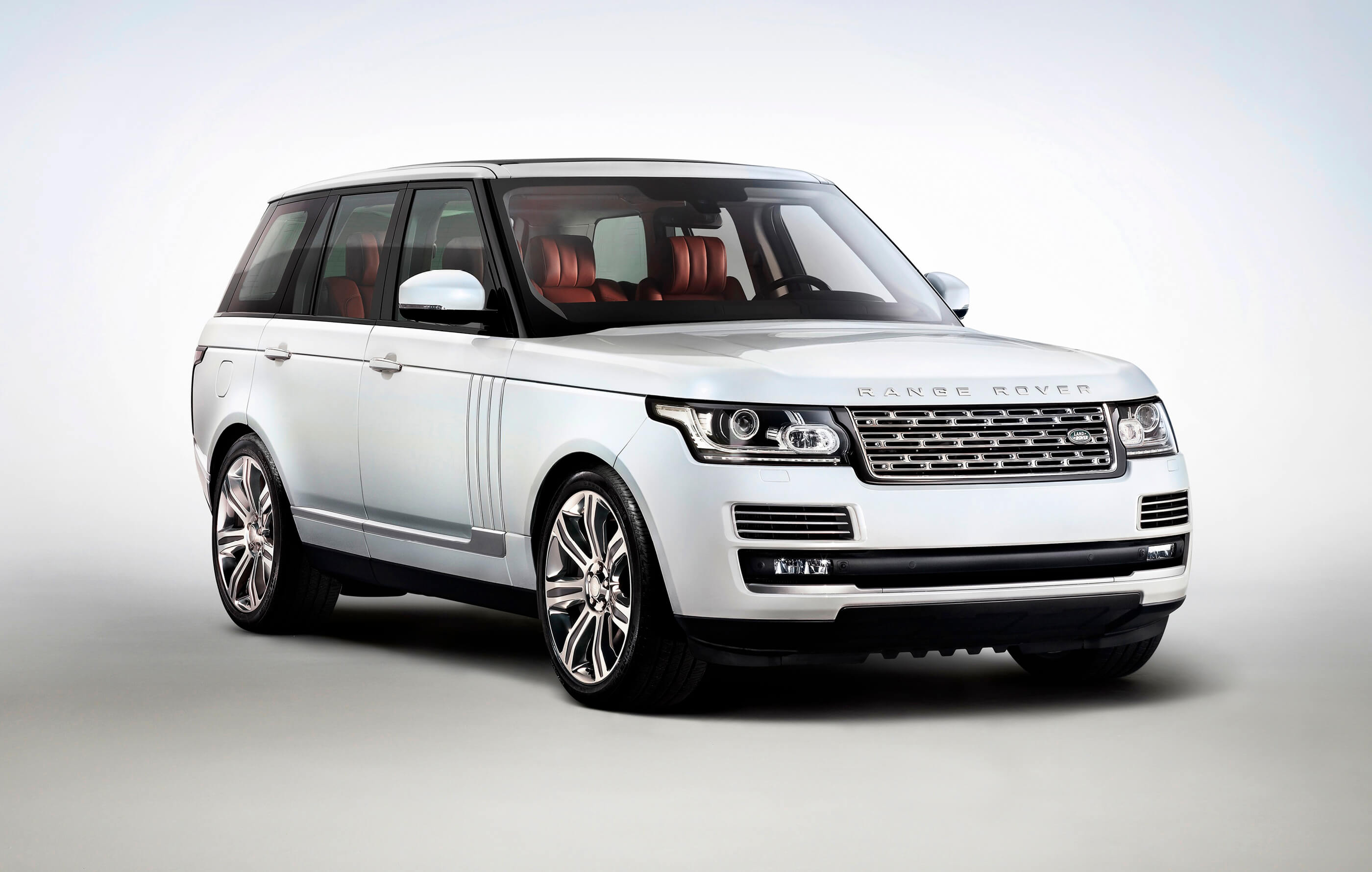 Full screen image of a white Land Rover Range Rover, with red leather interior on a white and grey background