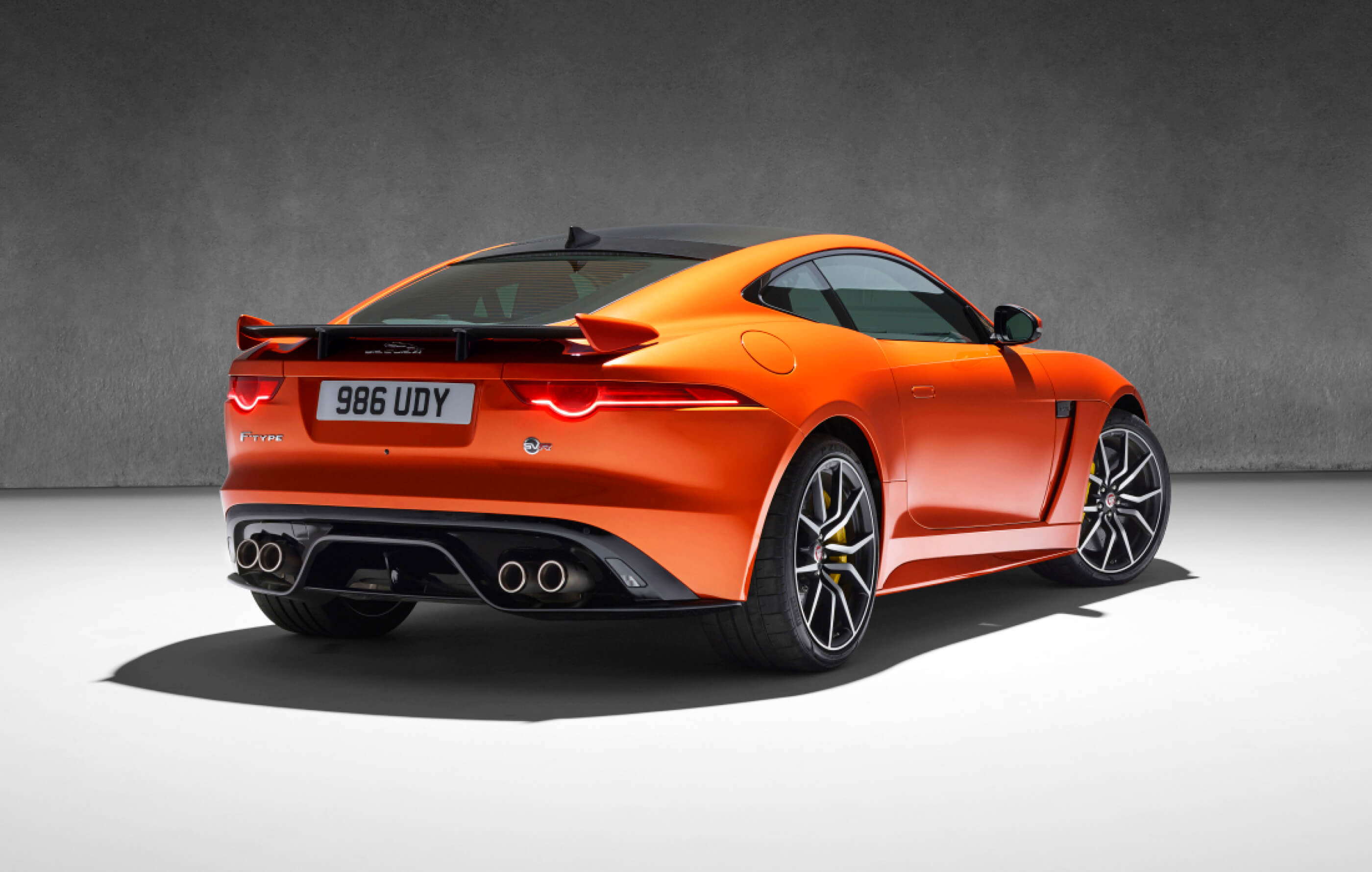 Full screen image of an orange Jaguar F-Type SVR, with tan leather interior on an industrial charcoal background
