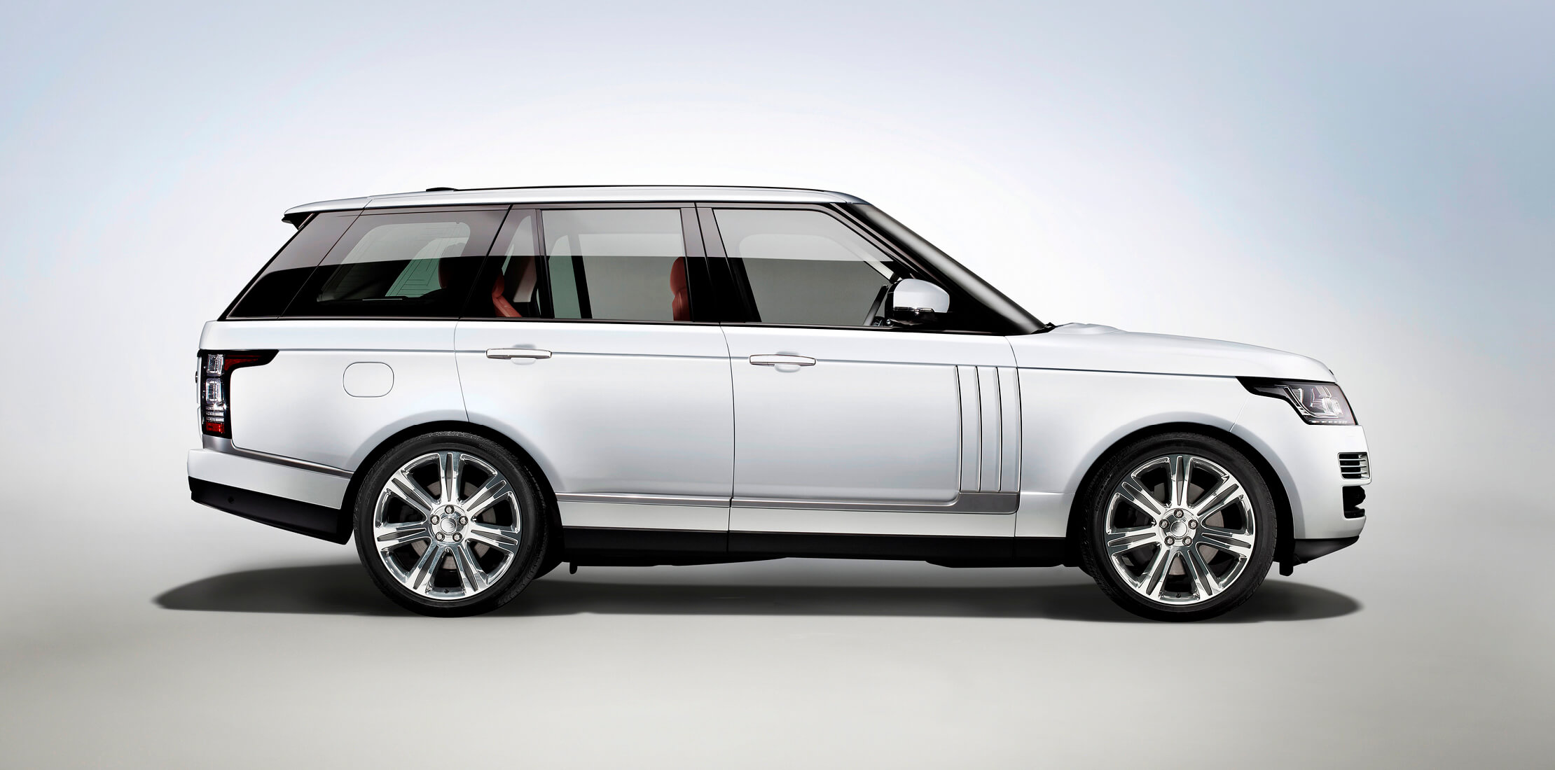 Profile shot of a white Land Rover Range Rover, with red leather interior on a blue and grey background