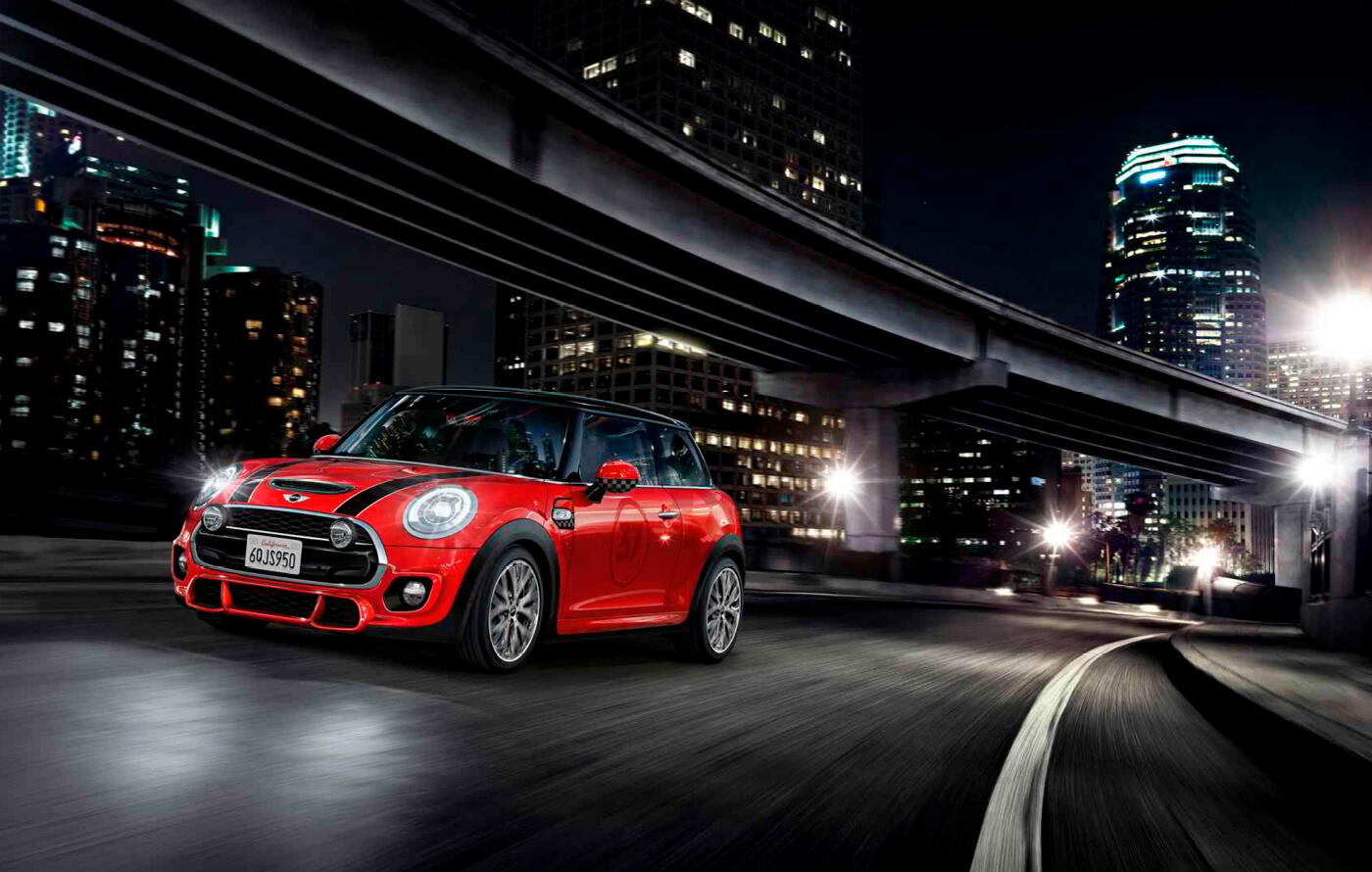 Full screen image of a red Mini John Cooper Works, racing along an urban street at night