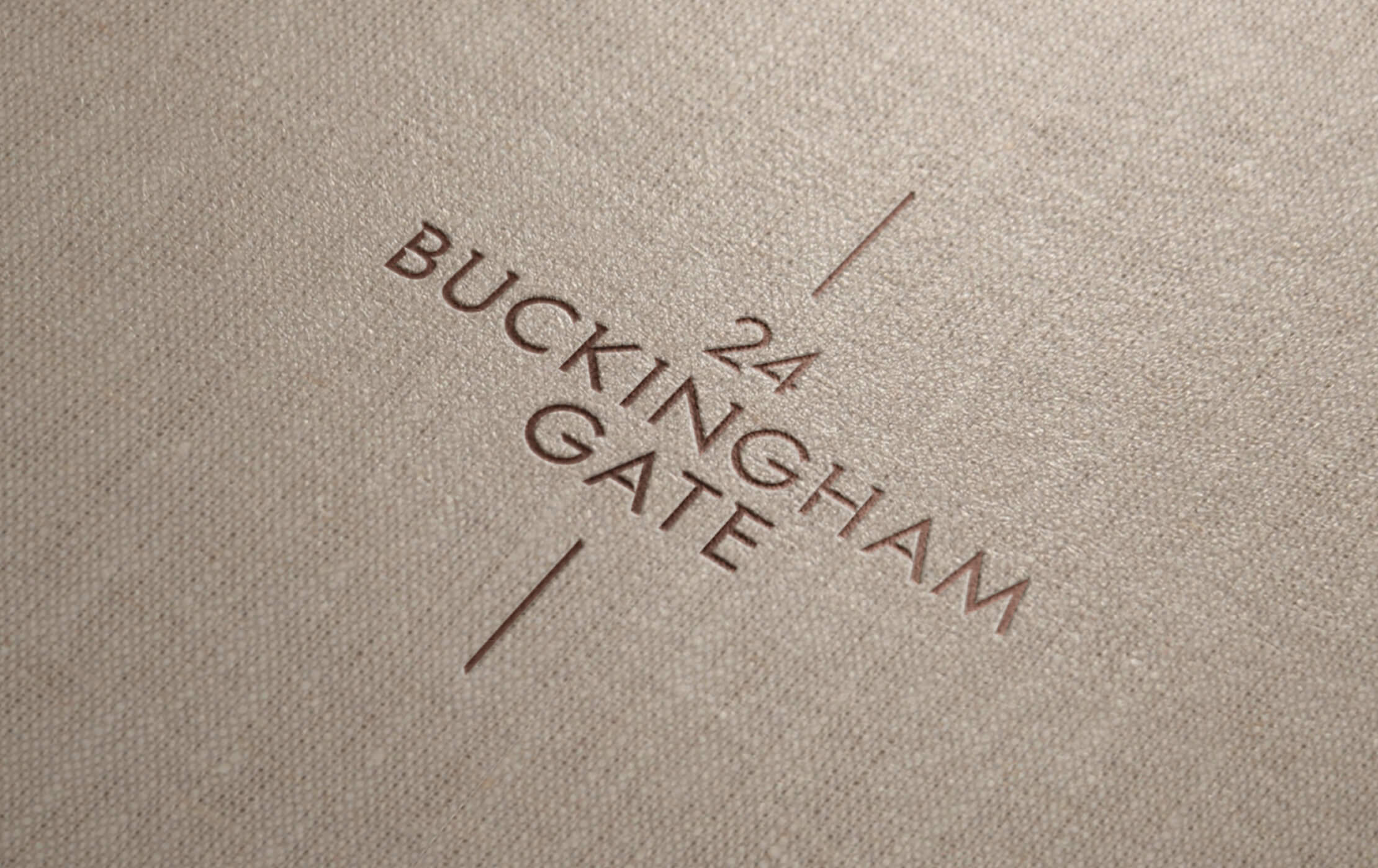 Brown and gold 24 Buckingham Gate logo embossed onto a cloth wrapped brochure cover