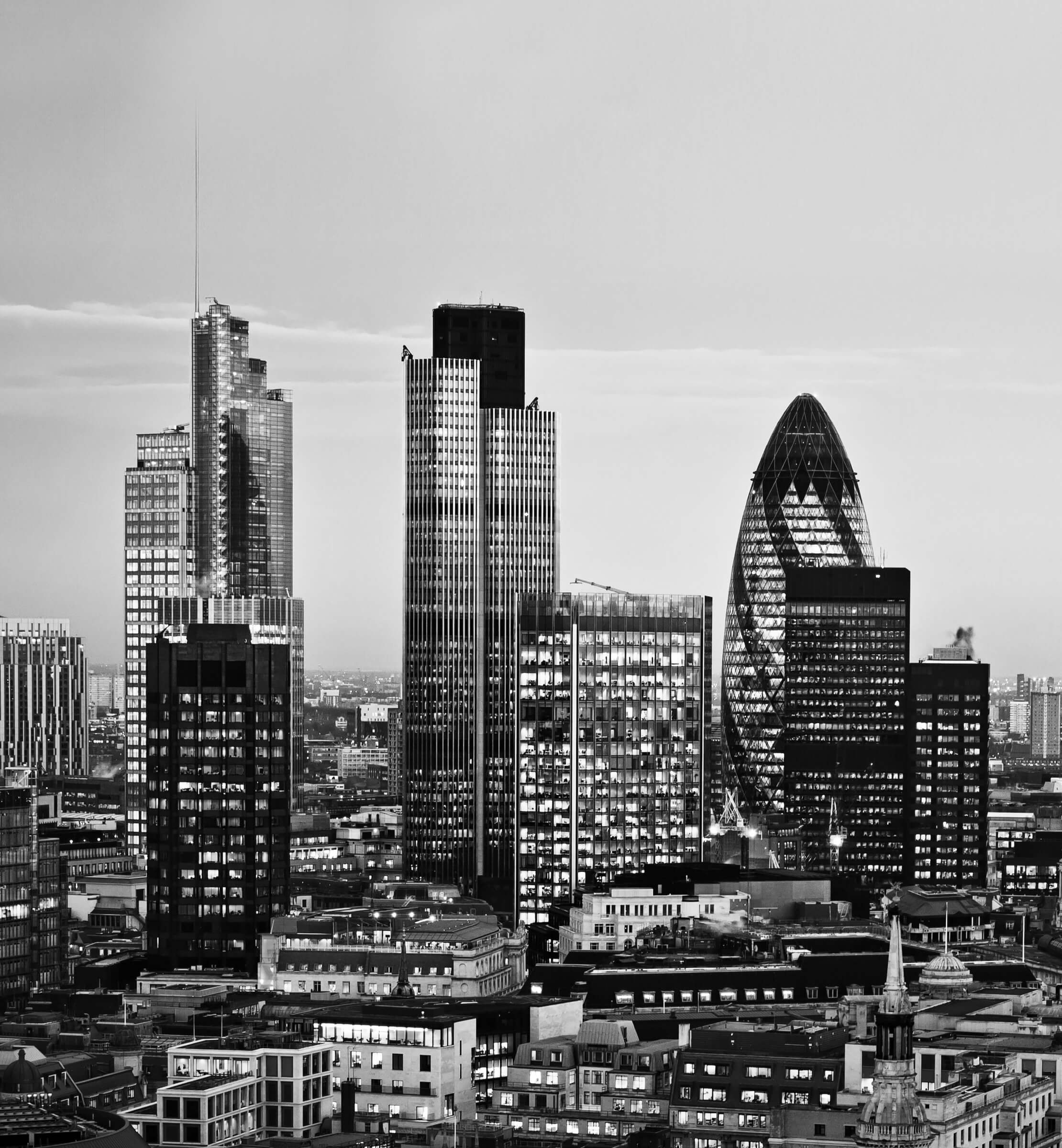 Black and white image of a cityscape of London, including the Gherkin, Tower 42 and Canary Wharf