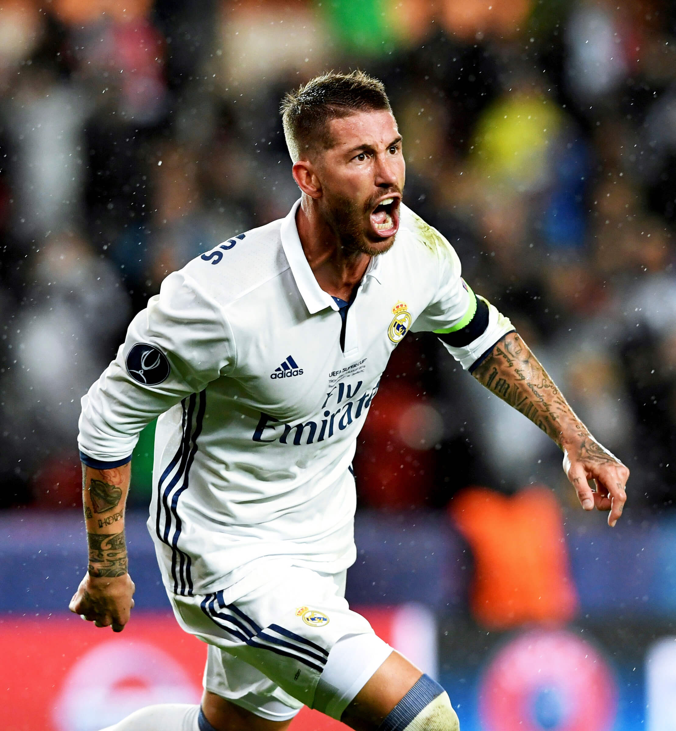 Real Madrid footballer Sergio Ramos wearing a white football shirt and captain's armband, celebrating after scoring a goal