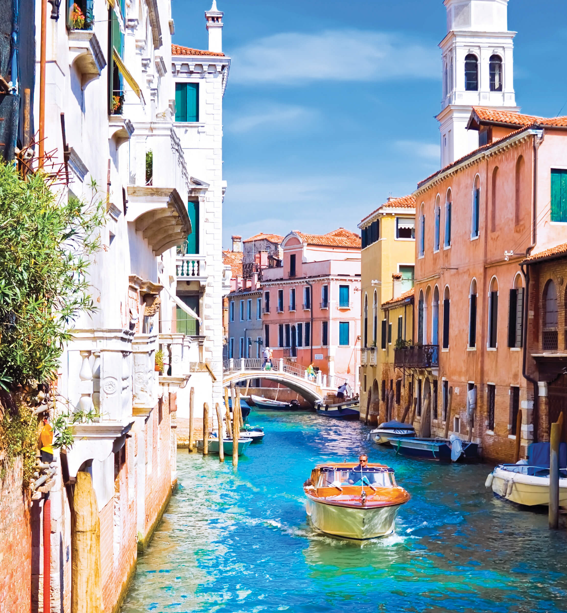Sunny shot of a canal in Venice, with boats moared along its sides and a small stone bridge in the background